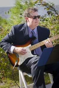 Teacher Drew Thompson playing guitar by the beach